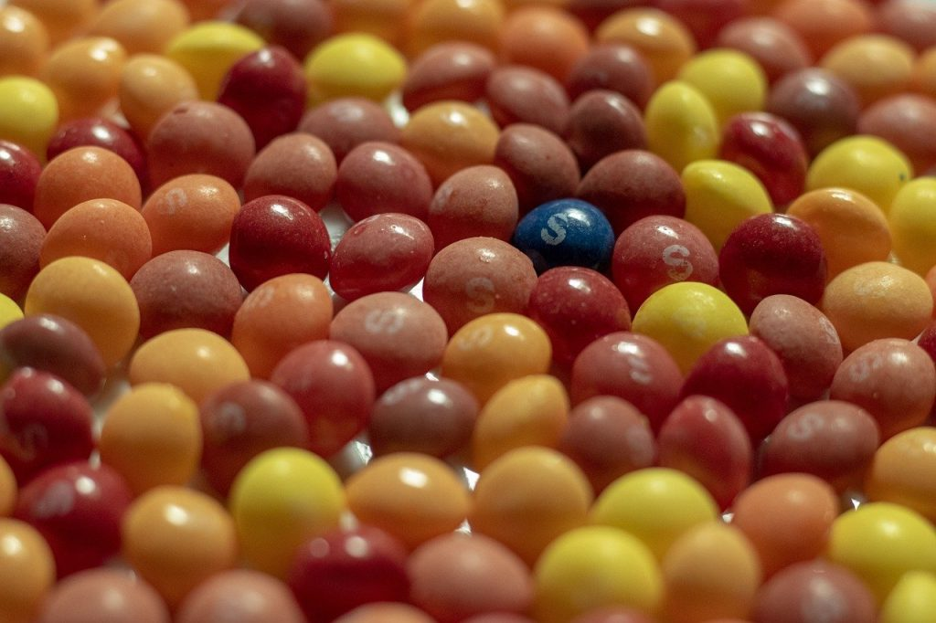 A bunch of red, yellow, pink, and orange Skittles with one blue one sticking out
